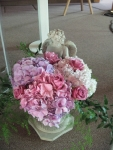 Garden statue filled with roses and hydrangea